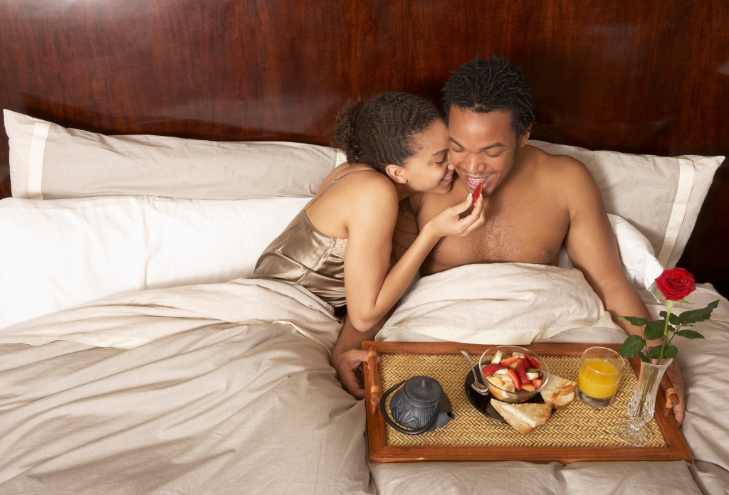 Woman feeding food to man in bed