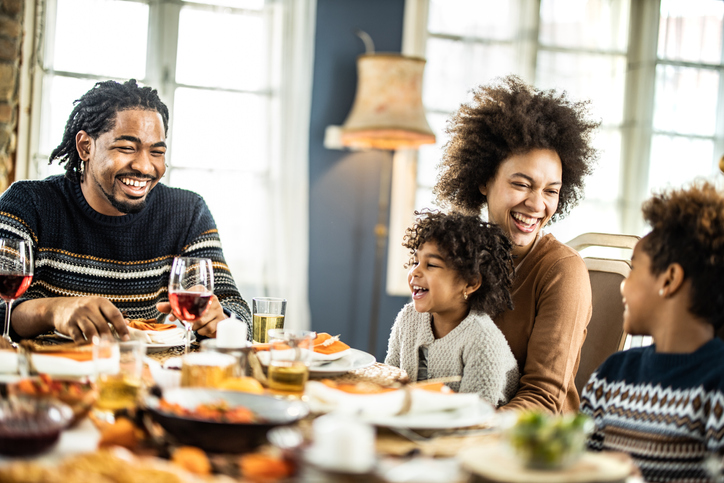Happy African American talking during lunch at dining table.