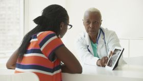 Black doctor using digital tablet with patient