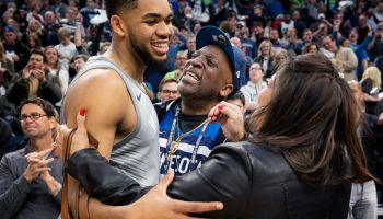 Timberwolves player Karl Anthony Towns hugs his parents after a game.